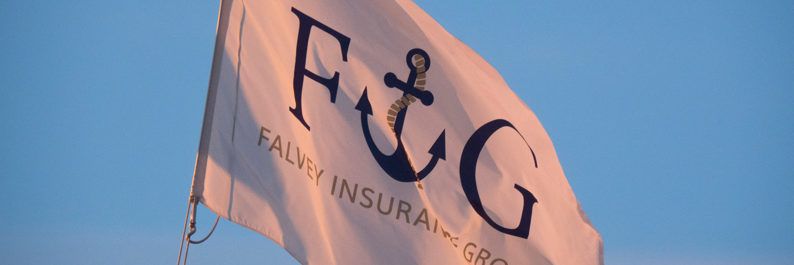 A flag representing the Falvey Insurance Group marine insurance mission is waving in the breeze
