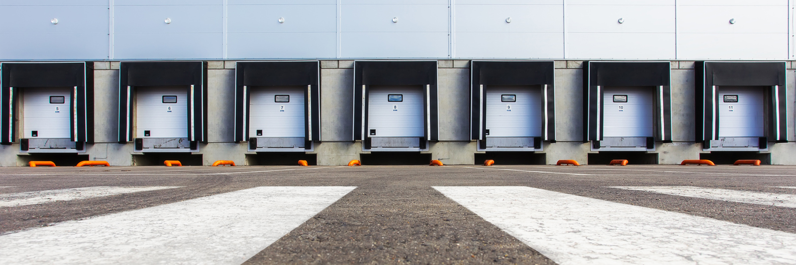 A row of parking spots at a shipping warehouse protected with shippers insurance wait for semi trucks to arrive